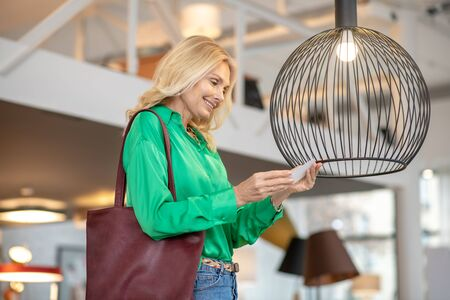 The bird. Blonde woman in a green blouse looking at the bird
