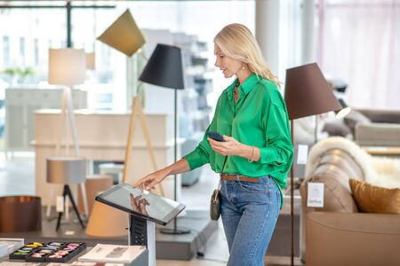 Gadget, furniture salon. Woman in a green blouse and jeans, standing near the tablet, a smartphone in one hand, the other hand above the screen of the device, watching, choosing.