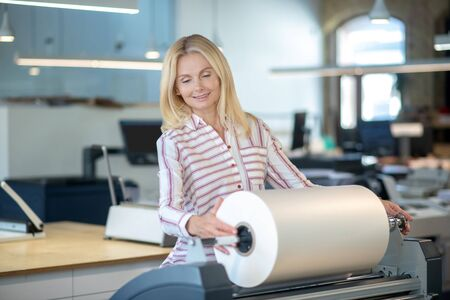 At workshop. Blonde woman standing at paper roll machine, checking the roll Stock Photo