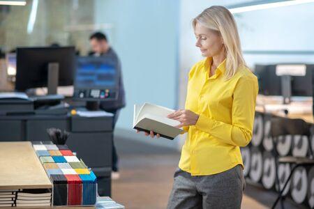 At workshop. Blonde woman standing, flicking through notebook, smiling