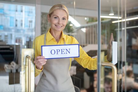 Indoors. Blonde woman opening glass door, holding sign saying open