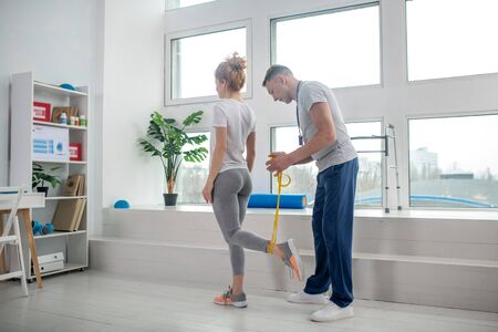 At rehabilitation center. Male physiotherapist and female patient doing exercises with resistance band