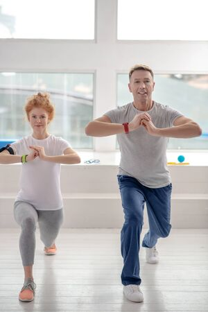 At rehabilitation center. Female patient and male physiotherapist lunging synchronically Standard-Bild