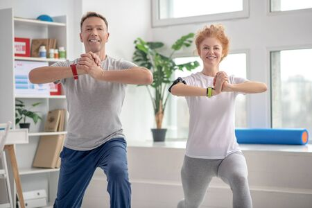 At rehabilitation center. Female patient and male physiotherapist lunging synchronically, smiling Standard-Bild