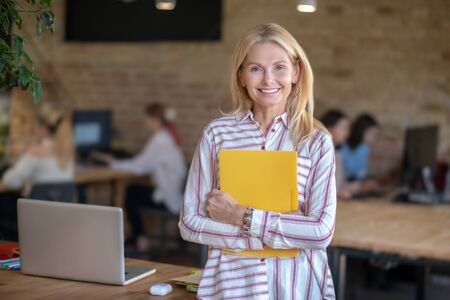 Modern office. Blonde woman standing in the office, holding yellow folder 写真素材