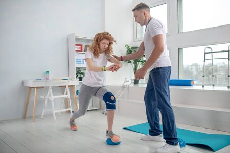 At rehabilitation center. Male physiotherapist helping female patient with lunging