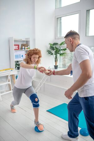 At rehabilitation center. Male physiotherapist supporting female patient with lunging Standard-Bild