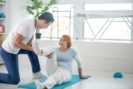 Medical assistance. Nice pleasant woman having her leg supported while doing the rehabilitation exercise