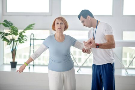 Special physical training. Pleasant aged woman trying to hold balance while being supported by her doctor