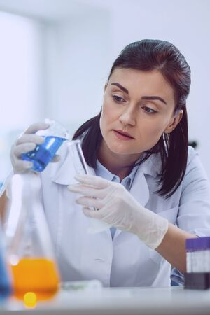 New discoveries. Determined dark-haired researcher carrying out a test while working in the lab on the coronavirus reseacrh