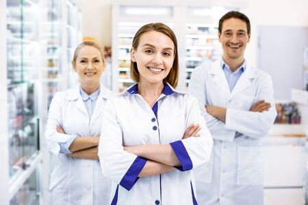 Welcome in drugstore. Cheerful reliable three pharmacists standing arms crossed, ready to advise and provide services.