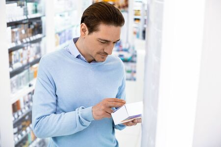 Recommendation for usage. Attentive serious man standing in a pharmacy holding medicine reading instructions for use 版權商用圖片