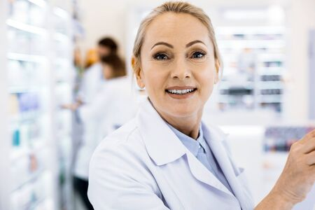Medical worker. Attractive smiling adult woman in a white medical coat standing in a pharmacy.