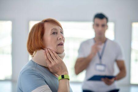 Feeling awkward. Good looking senior woman feeling awkward while having a neck collar on her