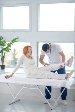 Medical examination. Nice aged patient sitting on the medical bed while having her leg examined