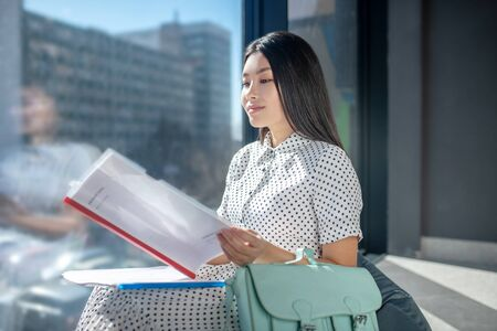 Business lady. Pretty young dark-haired businesswoman looking serious and looking through the documents