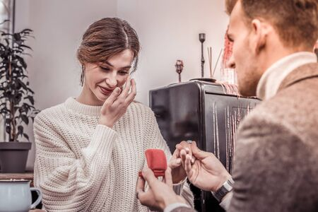 Surprised engaged woman shedding happy tears after being proposed on a good day