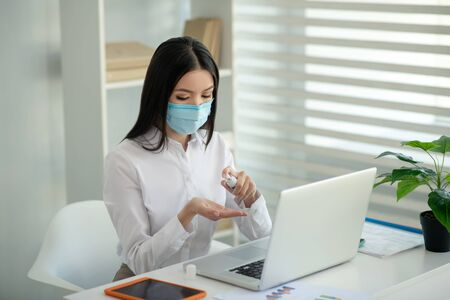Cleaning. Dark-haired woman in a facial mask spraying disinfector on her hands