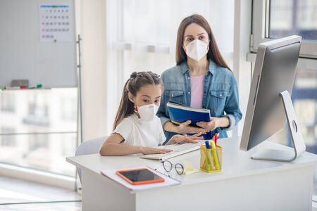 Protective mask, quarantine. Little schoolgirl sitting at a computer next to a woman, both in protective masks looking at the monitor.