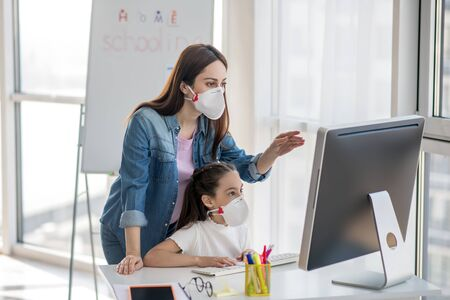 Caution virus. Standing woman pointing with hand at monitor and girl sitting at table, both in protective masks looking at computer. Foto de archivo