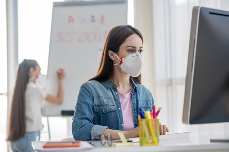 Studying during quarantine. Young woman in a protective mask and in a denim jacket sitting and looking at a computer monitor, behind a standing girl writing on a blackboard.