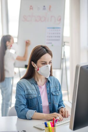 We work and study. Attentive woman in a protective mask working on a computer, standing behind a girl writing on a whiteboard, studying.