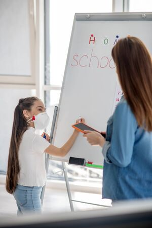 Educational process. Schoolgirl in a protective mask is interested in writing on a blackboard near a woman with her back standing next. Stockfoto