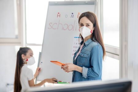 During quarantine. Young woman in a protective mask in a denim jacket with a tablet in hands standing near the girl who is wiping the board.