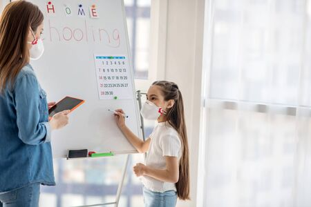 Home schooling. Long-haired girl of primary school age in a protective mask standing at the blackboard looking at a woman in jeans clothes with a tablet in her hands.