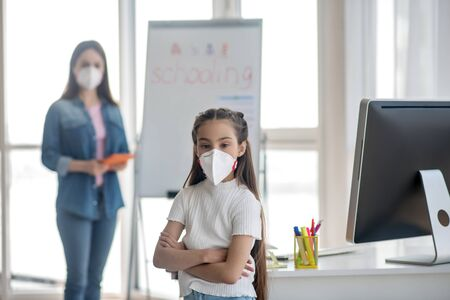 Kovid-19, quarantine. Cute girl with long hair in a protective mask standing near the table, a woman in a mask with a tablet near the blackboard.