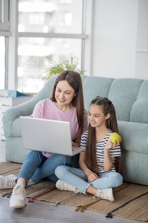 Good time. Mom with a laptop and daughter with an apple sitting on the floor near the sofa looking at the screen, smiling. Stockfoto