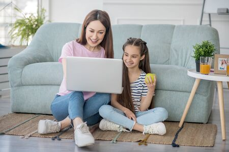 Interesting occupation. Young mother with a laptop and a school-age daughter with an apple, sitting on the floor looking at the screen, joyful.