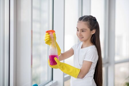 Cleaning. Long-haired teenager girl in yellow rubber gloves standing near a large window, in a good mood.