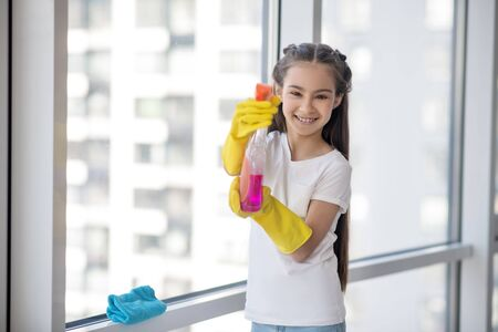 Cleaning. Cheerful teenager girl in a white tshirt with a window cleaner in her hands, laughing joyful. Imagens