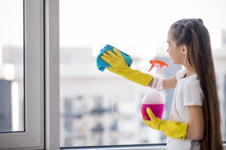 Little mistress. Long-haired girl in a white tshirt and yellow rubber gloves washing the window with a blue napkin, standing with back. Imagens