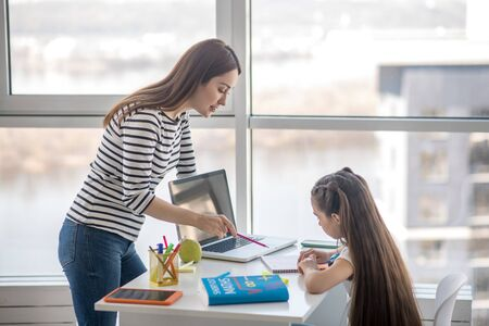 Learning process at home. Young pretty mother standing in front of a table pointing with a pencil to a notebook, telling her daughter a lesson.