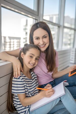 Happy together. Smiling mother and daughter in casual clothes sitting on the floor under a large window at home, together in a good mood.