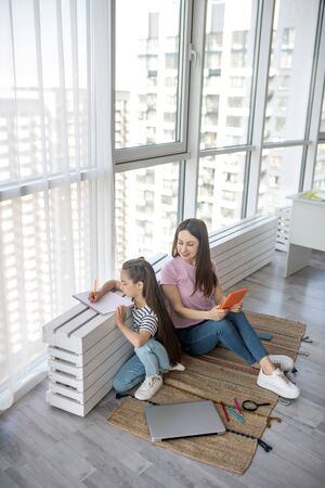 Home, quarantine. Young pretty mother with a tablet, daughter of primary school age writing in a notebook, sitting under a large window on the rug. Stockfoto