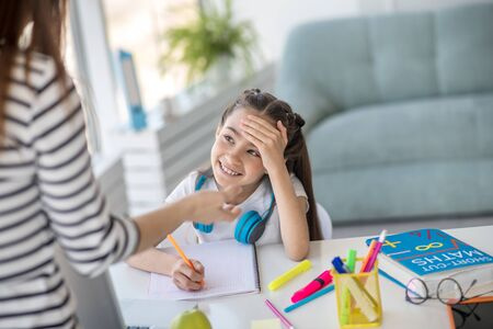 Time to learn. Little smiling girl schoolgirl sitting at the table with textbooks, looking at her mother standing in front, in a good mood. Stockfoto