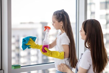 Learning to wash window. Daughter teenager in yellow gloves washing the window and mom standing closely looking and prompting, together doing the cleaning.