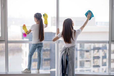 Clean windows. Young mother with her teenage daughter washing together a large window at home, standing with their backs.