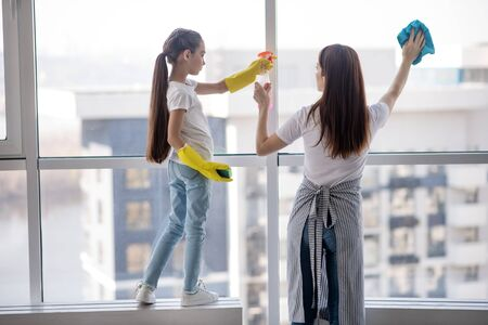 House cleaning. Daughter in jeans and rubber gloves standing on a windowsill holding a cleanser to mom, both washing the window.