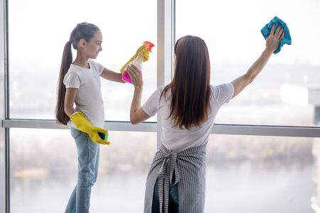 General cleaning. Mom in an apron and daughter in rubber gloves doing spring cleaning at home, washing a large window.