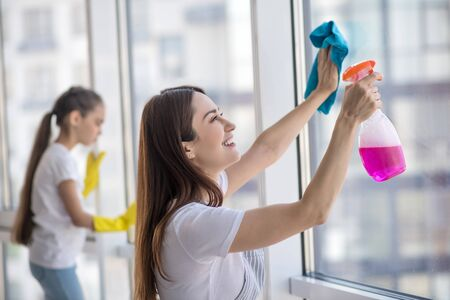 We love cleanliness. Young smiling mother with a rag and cleanser and daughter in gloves washing a window together. Stockfoto