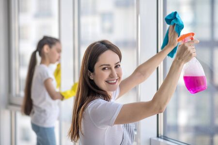 Cleanliness is the key to health. Young joyful mom with a blue napkin and pink detergent smiling turning her head and daughter washing a window.