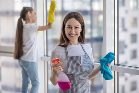 Excellent result. Satisfied happy young mother with a rag and detergent in her hands and daughter washing a window, rejoicing at an excellent result.