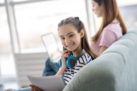 Great mood. Cheerful girl watching turning her head, holding a notebook in her hands, sitting with her busy mom on the couch. Stockfoto
