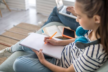 Occupation at home. Long-haired concentrated girl of primary school age with headphones writing in notebook while sitting on sofa, next to mom with laptop. Stockfoto