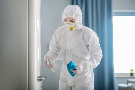 Room disinfection. Person in white workwear and gloves disinfecting the surface of the fridge