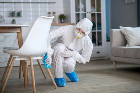 Chair cleaning. Woman in white workwear and gloves cleaning the chair